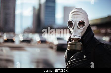un joven informal en una máscara de gas mirando la cámara