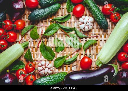 Varias verduras frescas sobre un fondo de ratán. Concepto de comida y cocina saludables. Foto de stock