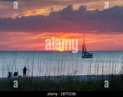 Velero en el Golfo de México al atardecer con un cielo naranja en la playa Nokomis en la costa del Golfo de Florida