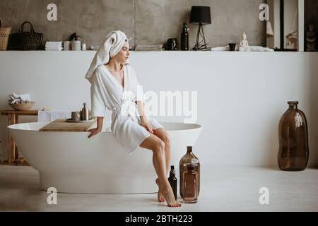 Atractiva mujer joven en un albornoz sentado en el borde de la bañera.