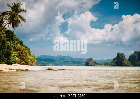 El Nido, Palawan, Filipinas. Paisaje tropical de laguna poco profunda, playa de arena con palmeras. Islas exóticas y un paisaje blanco nublado