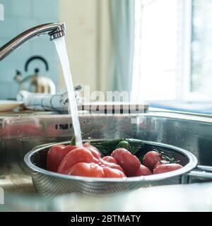 Verduras frescas bajo un chorro de agua en un colador en el fregadero, en la cocina, contra el fondo de una toalla y un Hervidor.