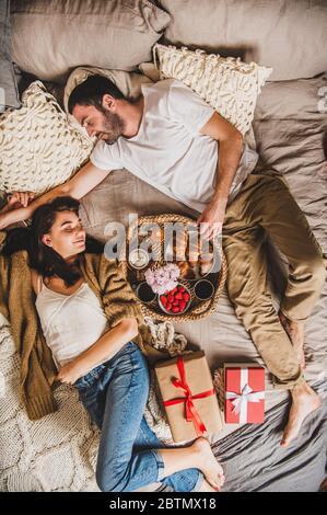 Feliz pareja sonriente acostada en la cama y tomando un desayuno festivo