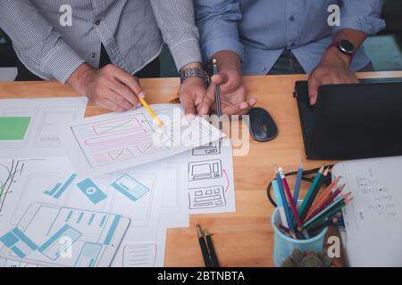 Diseñadores de UX o UI que diseñan en su proyecto prototipo de diseño de aplicaciones para smartphones.