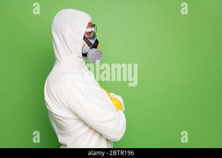 Primer plano vista lateral de perfil retrato de su él agradable contenido profesional desinfectante con máscara de gas anti sars n-cov-2 covid19 defensa brazos plegados