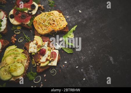 Variedad de sándwiches frescos y saludables con diferentes verduras, hierbas e ingredientes en mesa oscura