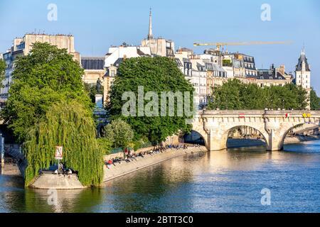 París, Francia - 14 de mayo de 2020: Vista de las personas sentadas y tomando el sol en las orillas del río Sena en la Isla de la Cite, cerca de Pont Neuf y la Plaza d