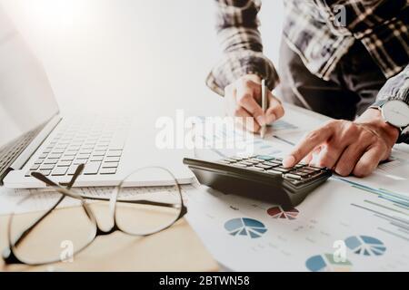 Hombre de negocios o contador que trabaja con ordenador portátil para calcular la financiación