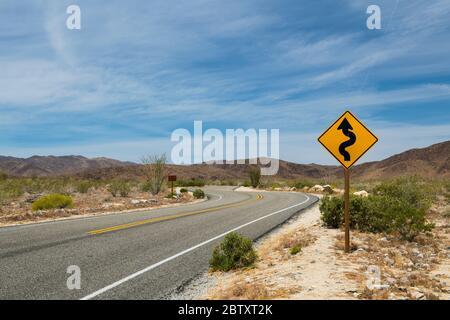 Una señal de carretera en una carretera a través del desierto en el Parque Nacional Joshua Tree, California, EE.UU.
