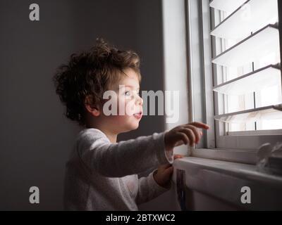 Un niño de dos años mira por la ventana