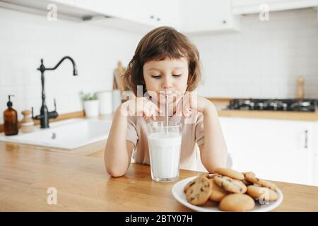 Linda niña pequeña bebiendo leche con paja de acero de vidrio y comiendo galletas sentadas en la mesa de la cocina. Reduzca el uso de plástico en casa con los niños
