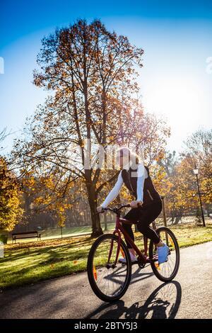 Ciclismo urbano - mujer montando bicicleta en el parque de la ciudad