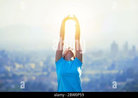 Joven deportivo sano en la montaña o en la cima de la colina en Murcia, España. Hábitos beneficiosos y estilo de vida. Chica viendo la puesta de sol sobre la ciudad, brazos abiertos
