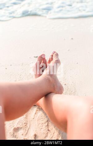 Pies de mujer en la playa de arena blanca en el agua poco profunda