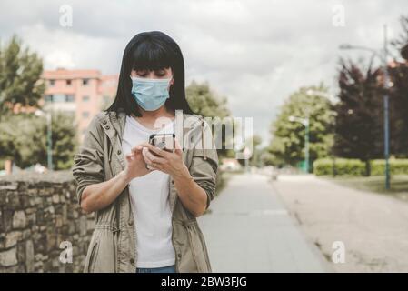 Mujer con máscara médica con su smartphone en la calle al aire libre