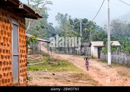 África, África Occidental, Togo, Kpalime. Un niño pequeño camina por una calle de tierra con un tazón en la cabeza. En el cielo, los murciélagos salen a la noche.