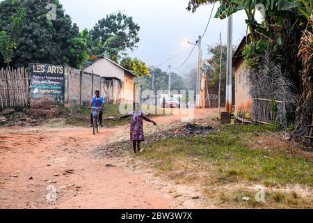África, África Occidental, Togo, Kpalime. Un niño pequeño camina por una calle de tierra. En el cielo, los murciélagos salen a la noche.