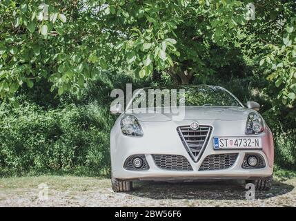 Limpio y brillante plata Romeo Alfa Giulietta estacionado bajo un árbol verde. Hermoso día soleado. Vista frontal de la parrilla de coche en la matrícula croata