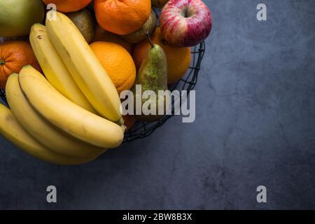 Manzanas, plátanos, peras, mandarinas y naranjas en un tazón de fruta sobre fondo de hormigón. Alimentos saludables. Vista superior. Espacio de copia.