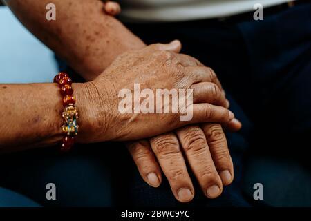 Cerca de la mano de una anciana que sostiene las manos de un anciano. Concepto de amor romántico duradero para siempre