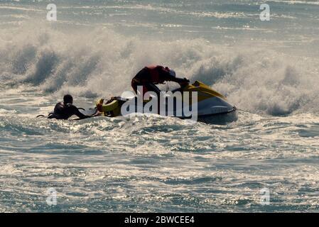 Los salvavidas RNLI rescatan a surfistas en la playa fistral un día después de reanudar los servicios en la playa Fistral Cornwall Reino Unido