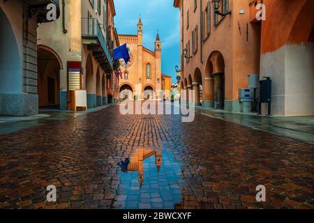 Pequeño charco en una calle adoquinada entre casas antiguas y la catedral de San Lorenzo al fondo en la ciudad de Alba, Piamonte, norte de Italia.