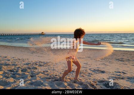 Niño feliz jugando en el mar. Niño divertirse al aire libre. Vacaciones de verano y concepto de estilo de vida saludable. Los niños juegan con arena en la playa de verano.