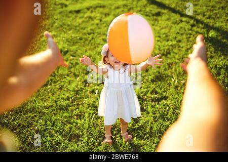 Feliz familia caminando en la hierba en el parque de verano. Madre padre y niños jugando en la naturaleza. Día De La Protección De Los Niños. Foto de stock