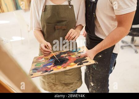 Retrato de sección media de tonos cálidos de pareja creativa pintando juntos el cuadro, centrándose en las manos sosteniendo la paleta y mezclando pintura, copiar espacio