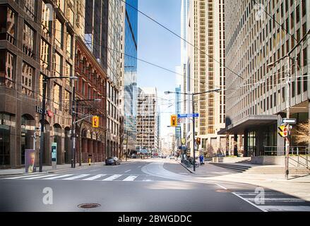 Toronto, Ontario, Canadá - 8 de abril de 2020: Centro de Toronto durante la pandemia del Coronavirus. Los transeúntes raros en la calle de Toronto durante la prisa nuestro.