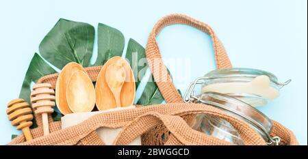 Juego sin plástico con bolsa de algodón, jarra de cristal, hojas verdes y vajilla reciclada vista superior. Cero residuos, concepto ecológico. Disposición plana.