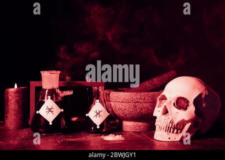 Pociones, cráneo humano, mortero y pedrería en la mesa del alquimista