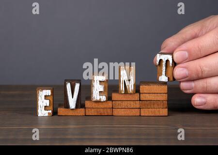 EVENTO. Concepto de formación, foro, reuniones y oportunidades. Letras del alfabeto de madera en los escalones. Fondo gris