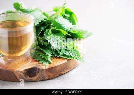 Taza de té de hierbas saludable con ortiga. Medicina herbaria alternativa. Ortigas picantes, urtica. Cuidado de la alergia de la piel. Ortigas frescas sobre el backgr gris