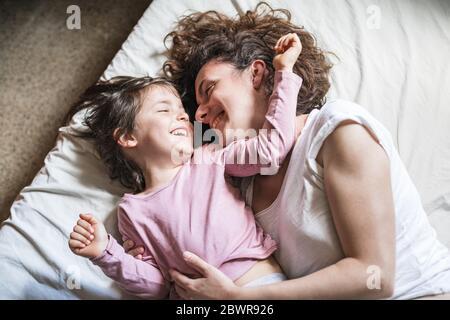 Una madre y su hija sonreían mientras se acarician y juegan en una cama.