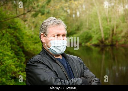 Hombre feliz de mediana edad en una máscara médica en un paseo por la naturaleza. El concepto de atención de salud y cuarentena.