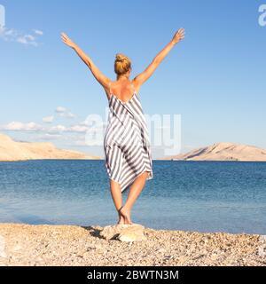 Feliz mujer sin preocupaciones subiendo los brazos, con un hermoso vestido de verano a rayas disfrutando a última hora de la tarde en la playa blanca de la isla Pag, Croacia