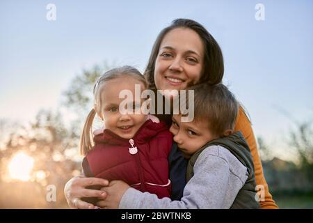 Retrato de madre feliz abrazando a dos niños al aire libre