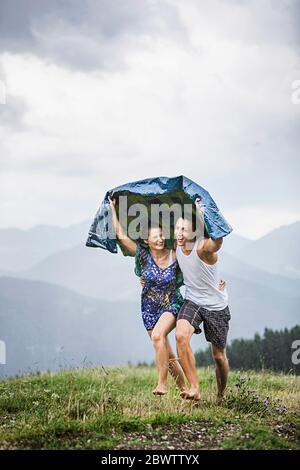 Feliz pareja corriendo en un prado en las montañas bajo la lluvia, Achenkirch, Austria Foto de stock