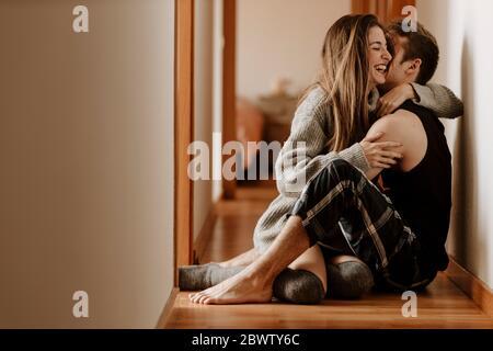 Feliz pareja joven sentada en el piso en casa Foto de stock