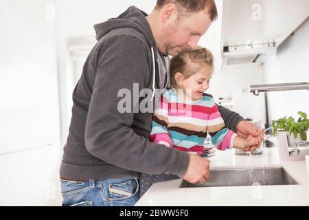 El padre y la hija se lavan las manos en la cocina