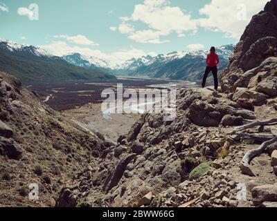 Vista trasera de toda la longitud de la mujer de pie sobre una roca admirando las montañas, el Chalten, Argentina