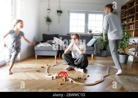 Estresado madre sentada en medio de juguetes, mientras los niños corren a su alrededor Foto de stock