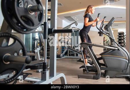 Vista lateral de la joven mujer en forma negro elegante encaje deporte ropa en bicicleta elíptica entrenador. Interior gris claro de fondo moderno gimnasio con diferente Foto de stock