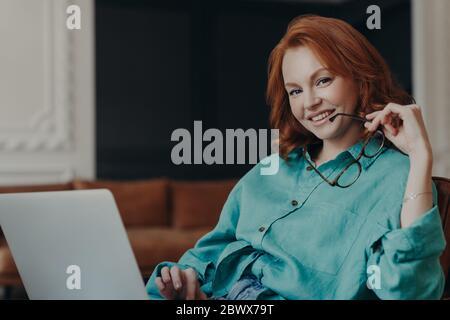 Positivo buena mujer joven que mira trabaja remotamente en computadora portátil, conectado a internet sin cables en casa, sostiene gafas, vestido adentro