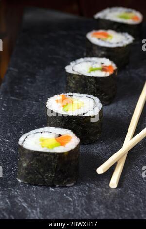 Cocina japonesa. Rollillo de sushi de salmón casero con aguacate y pepino en un plato de piedra oscura. Primer plano. Enfoque selectivo