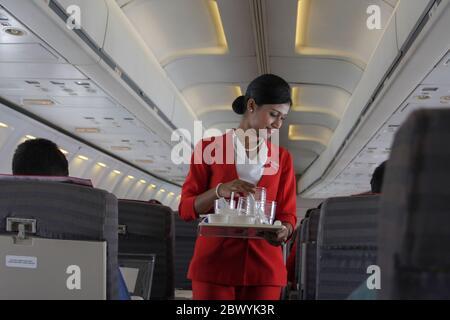 Un equipo de cabina recogiendo vidrio de agua usado en un avión de Best Airways. Bangladesh