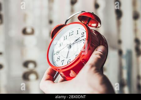 Causa tiempo, tiempo de descanso - UN hombre mantiene un reloj de alarma y muestra la hora - concepto - no perder el tiempo en vano
