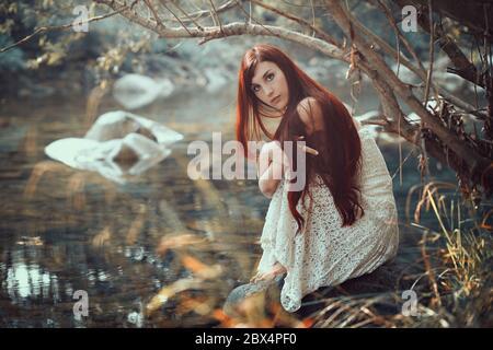 Hermosa mujer posando en una orilla de arroyo. Colores otoñales Foto de stock