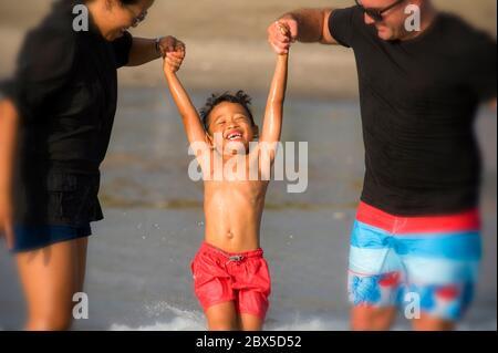 Joven feliz mezcla de etnicidad pareja hombre caucásico y mujer Indonesia asiática jugando en la playa tropical con el hijo pequeño los padres criando al niño Foto de stock